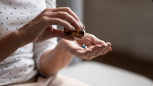 Woman putting ambien and Lunesta pills into her palm