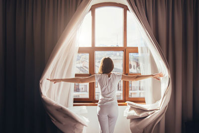 Woman looking out a window comparing inpatient and outpatient addiction treatment