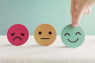 Happy, neutral, and sad faces on paper cutouts