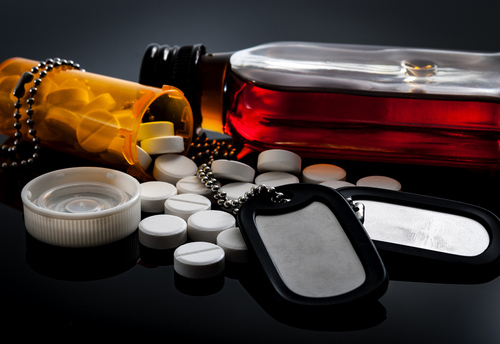 A veteran's dog tag next to drugs and alcohol